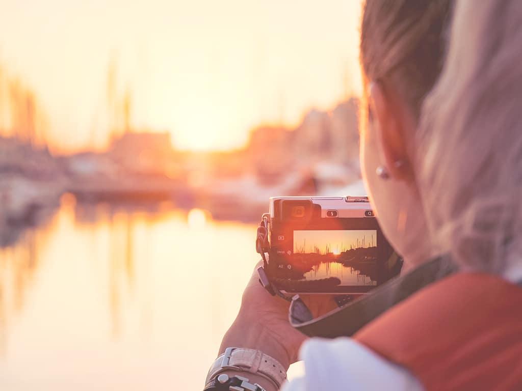 Frau mit Kamera fotografiert einen Hafen