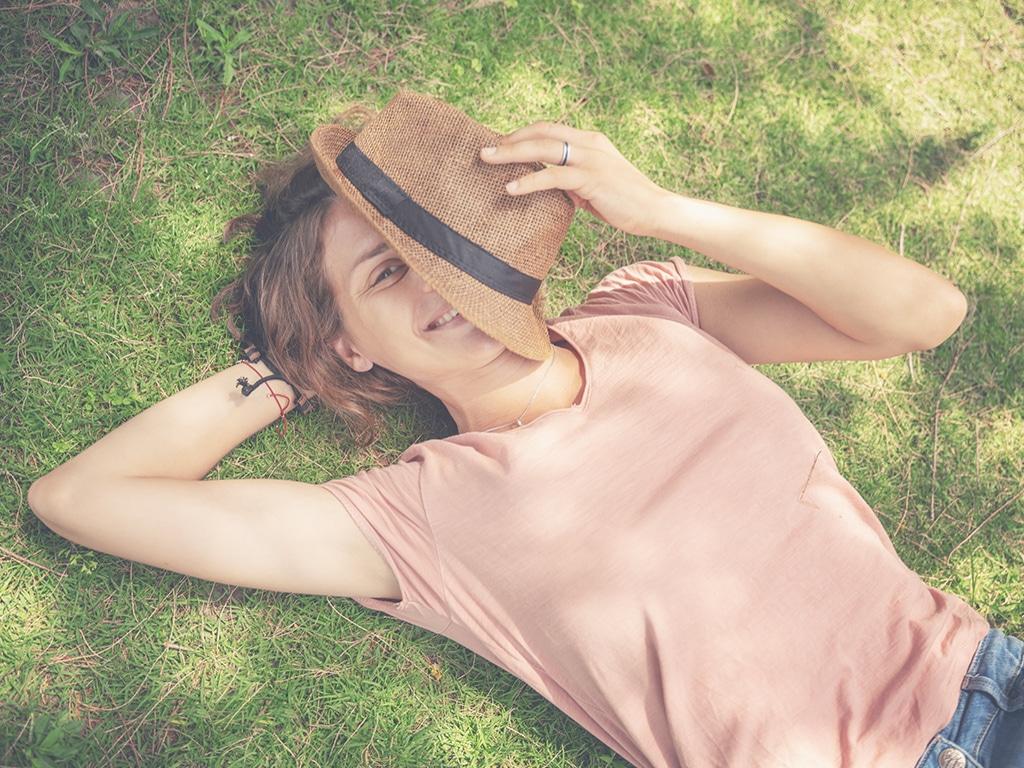 Frau liegt auf den Rasen mit einem Strohhut